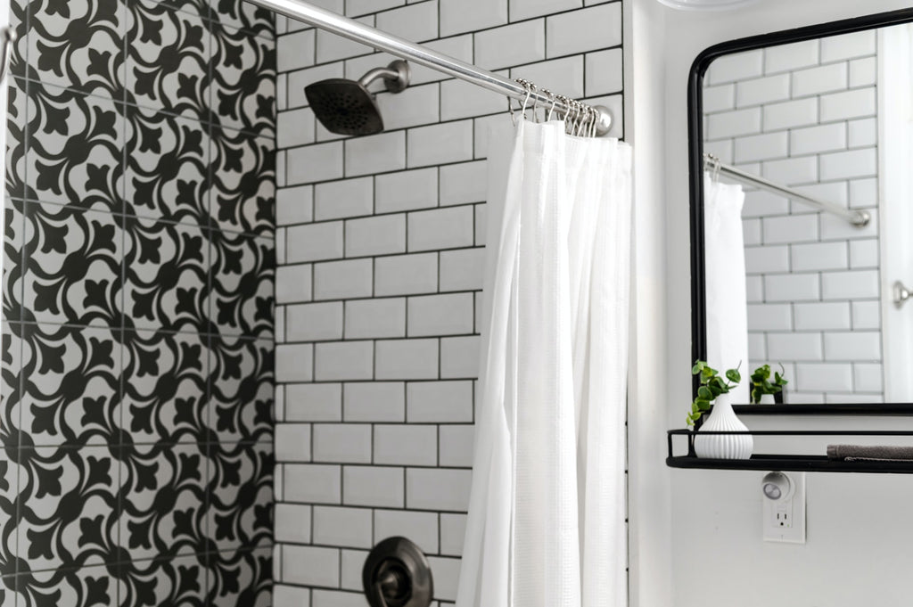 A bathroom is shown, focusing in on the open shower curtain and shower head.