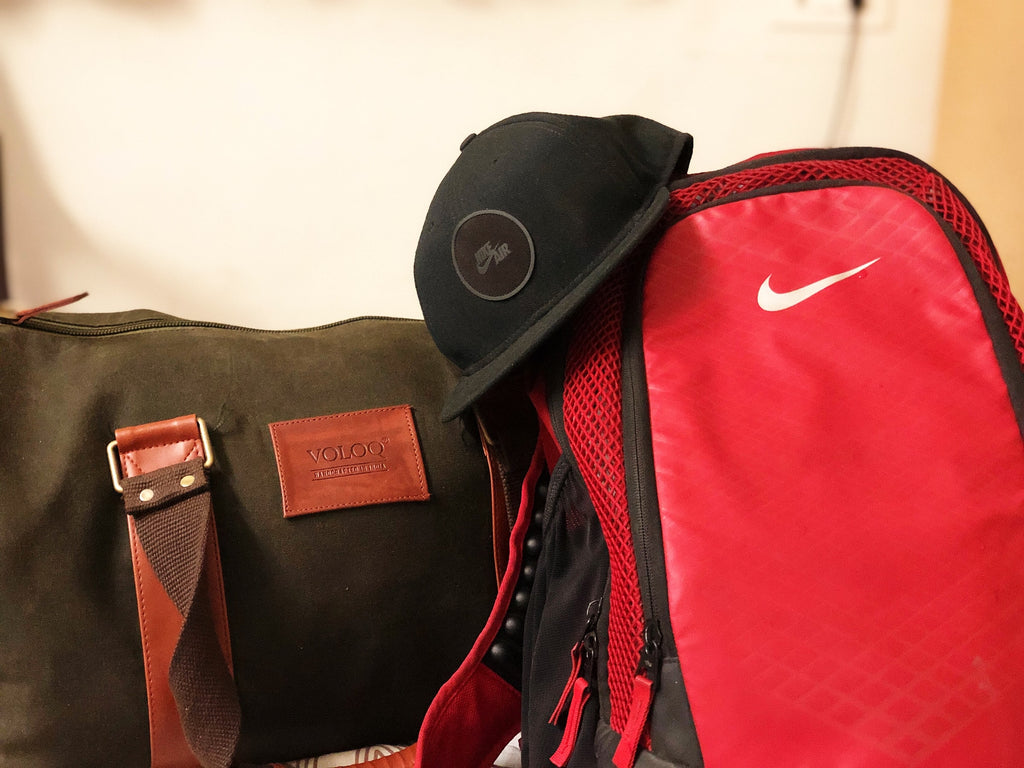 The image shows a red backpack, black baseball cap, and black and brown duffel bag.