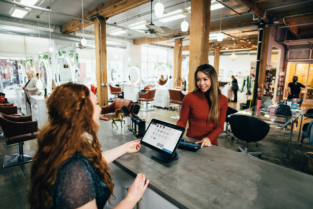 Two women stand on opposite sides of a counter using tablets to conduct work on the Internet.