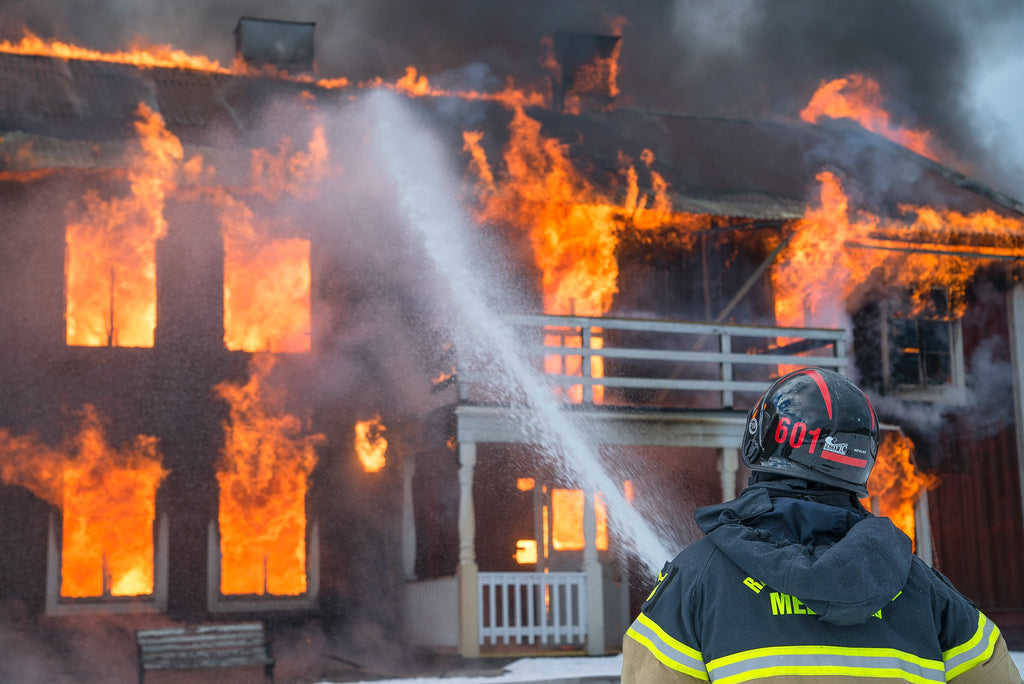 A firefighter sprays water on a building that is engrossed in flames.