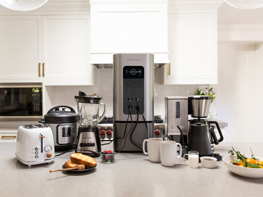 The HomePower 2 backup power station is on the kitchen counter surrounded by kitchen appliances it can be power, including a toaster, blender, crockpot, coffee machine, and tea kettle.