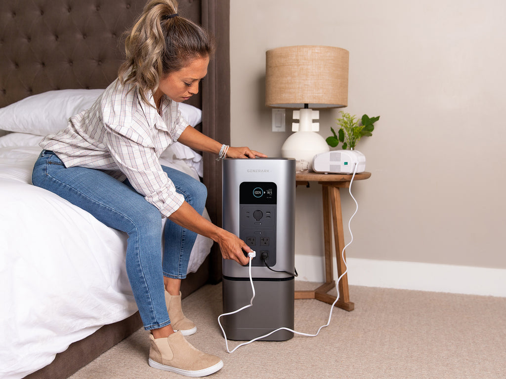 A woman plugs a medical device into the Generark HomePower 2 backup power station, which is sitting on the floor next to a bed.