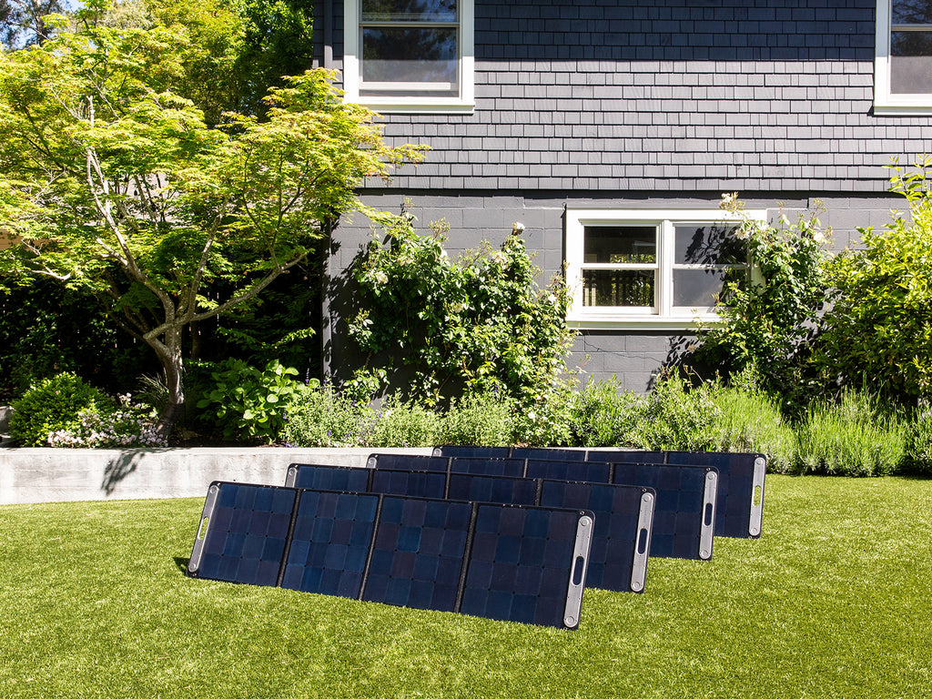 Four rows of SolarPower 2 solar panel generators are pictured set up in the grass of a lawn.