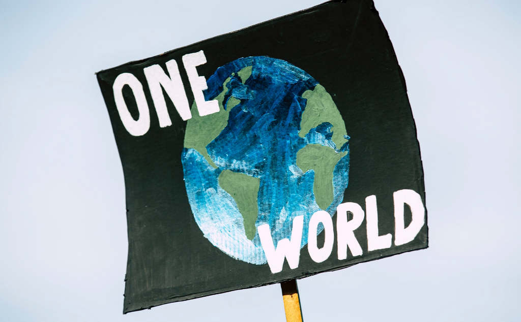 """A black sign has a painted image of the Earth on it and reads """"one world."""""""
