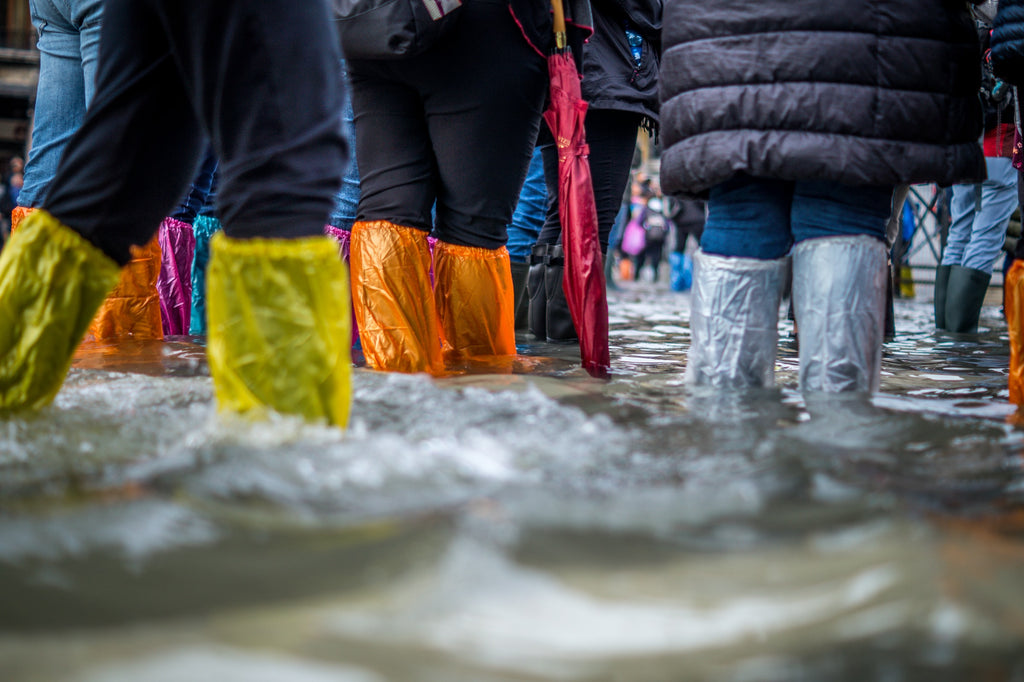 The picture depicts many people standing in flood waters while wearing long pants and rain boots covered in protective plastic.