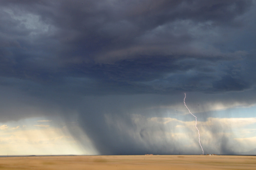 Powerful rain and lightning town down on a dry area of land.