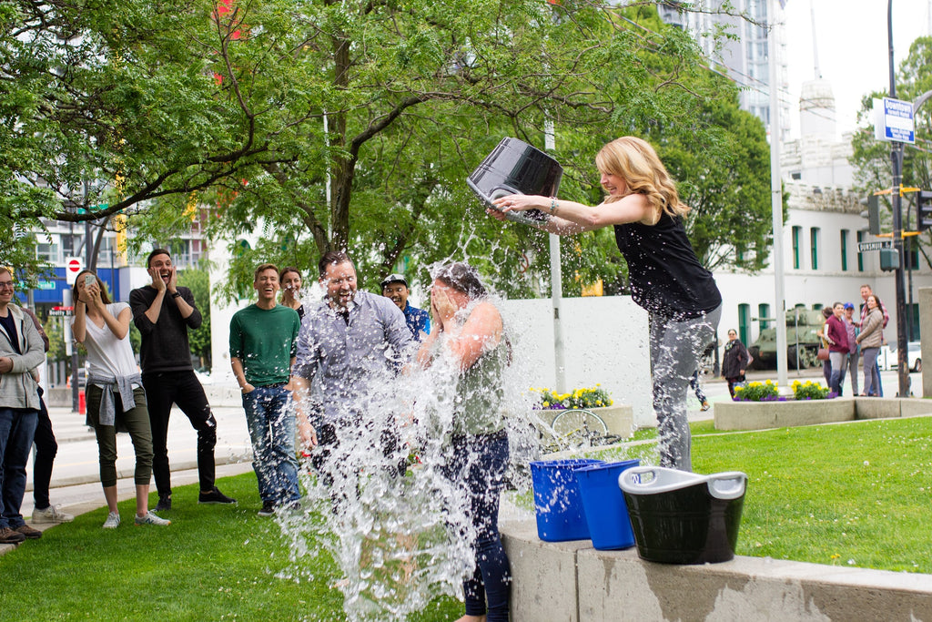 A woman dumps a bucket of water over a person's head while a crowd cheers them on.