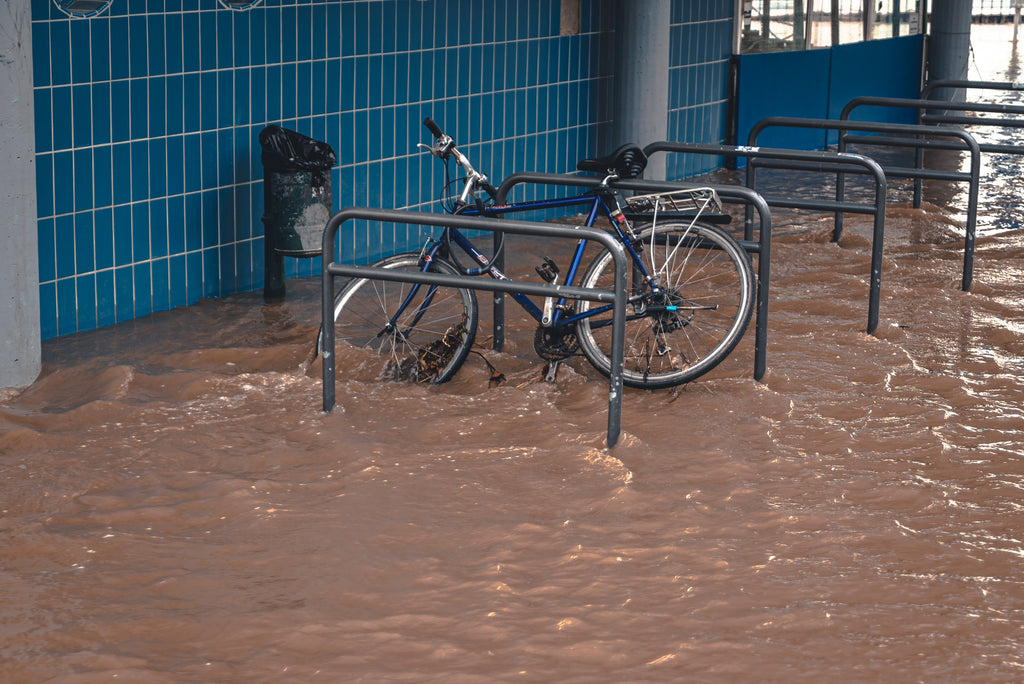 A bike leans against a bike rack with flood water covering the ground.