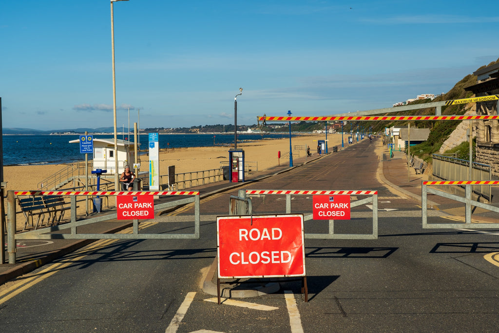 The image shows a road next to the beach with many traffic barriers and a sign reading road closed.