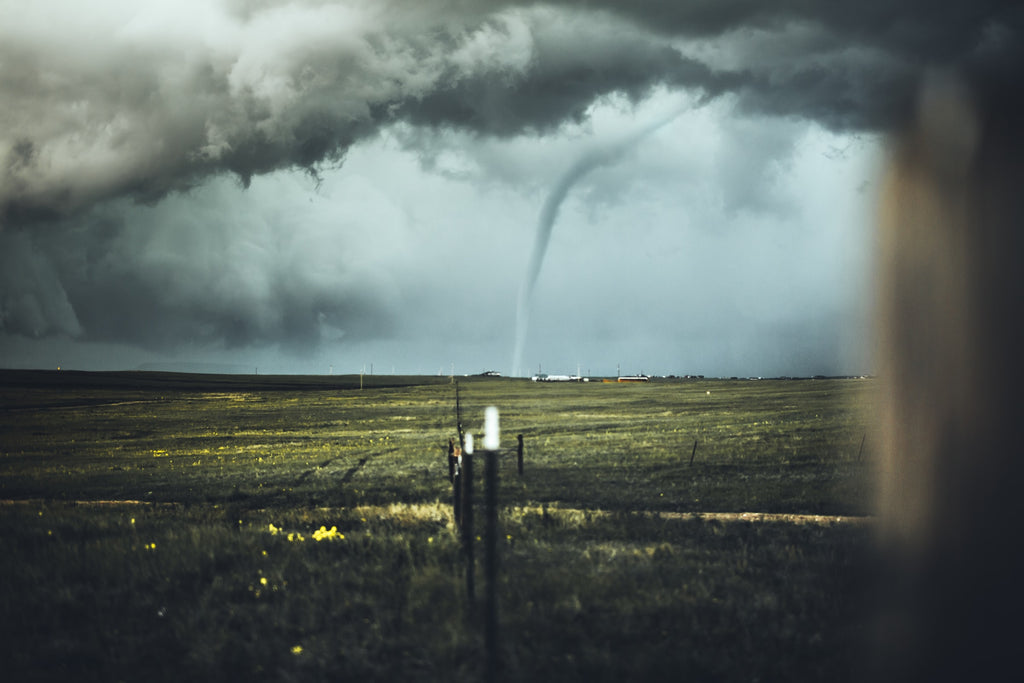 The image shows dark storm clouds over a field, with a tornado funnel in the distance.