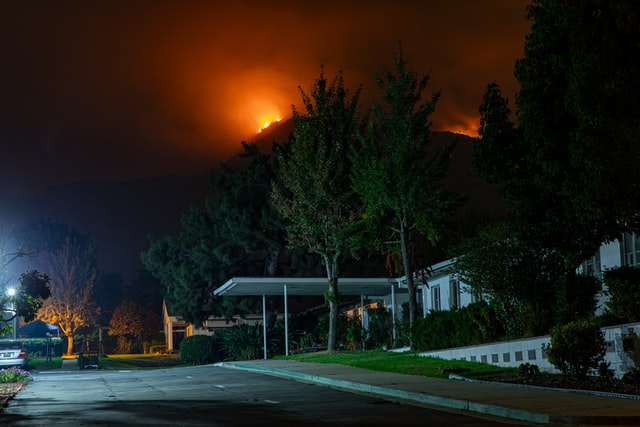 The image shows a neighborhood street with a wildfire's flames glowing behind the houses.