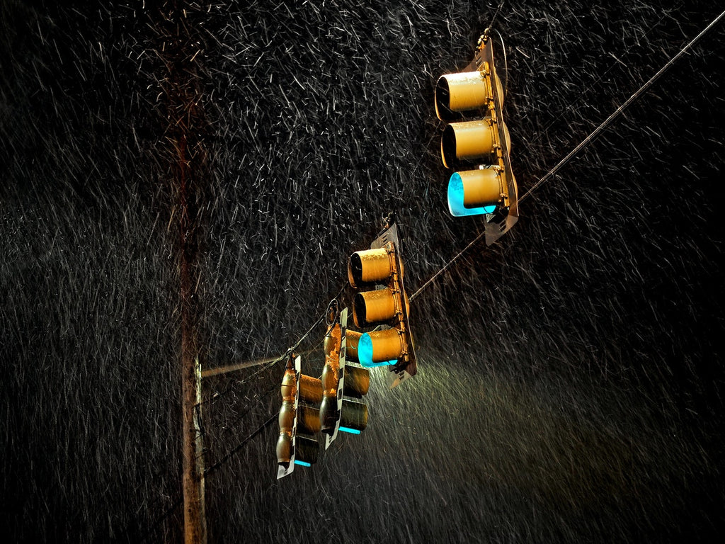Yellow traffic lights are shown while it is raining.