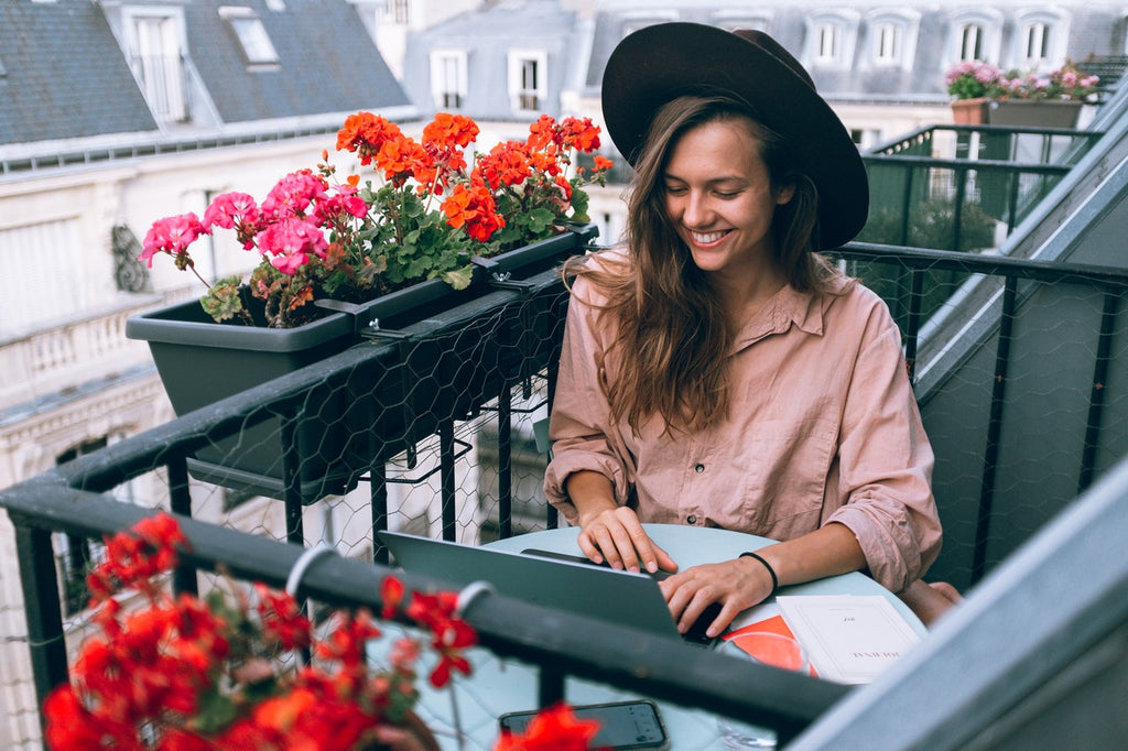 A woman works on a laptop while sitting on an outdoor balcony with flowers.