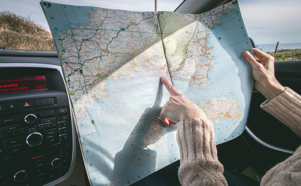 A woman sitting in a car points at a location on a paper map she is holding.