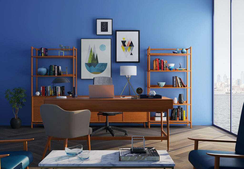 An office space shows a bookshelf with many picture frames and knick knacks on a wall behind a desk.