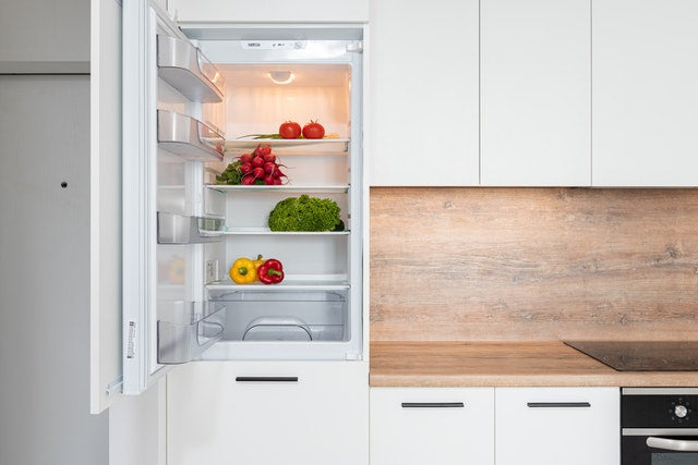The refrigerator door is open in a home kitchen, showing produce and food items organized within it.