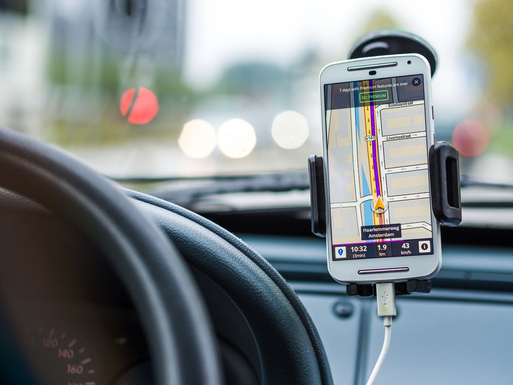A cell phone is plugged into a car acting as a GPS.