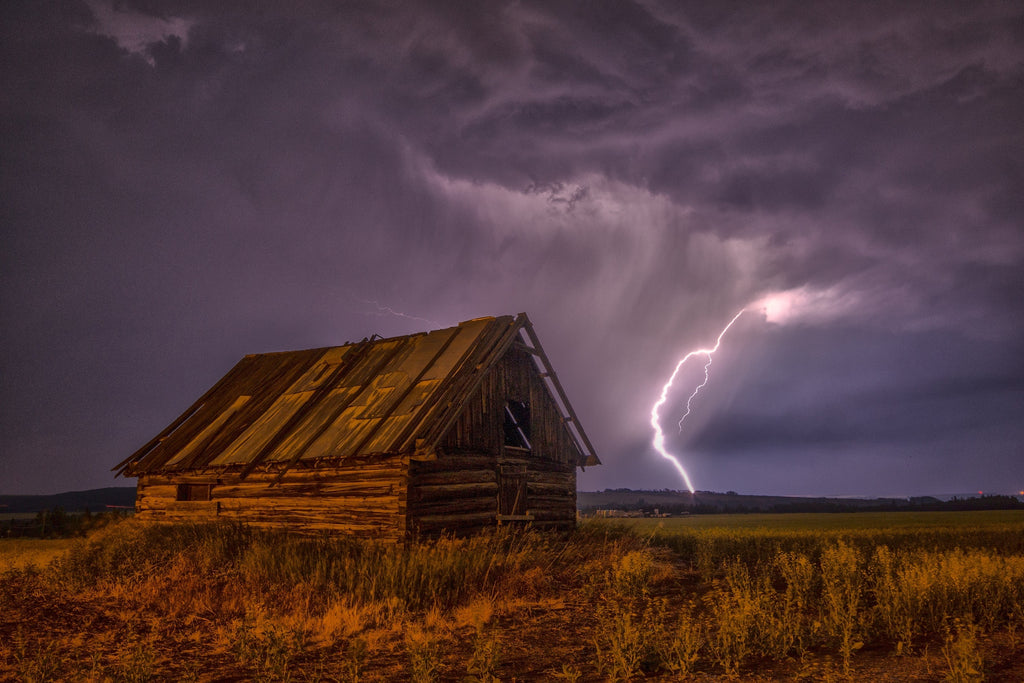 During a rain storm lightning hits the ground behind a small house.