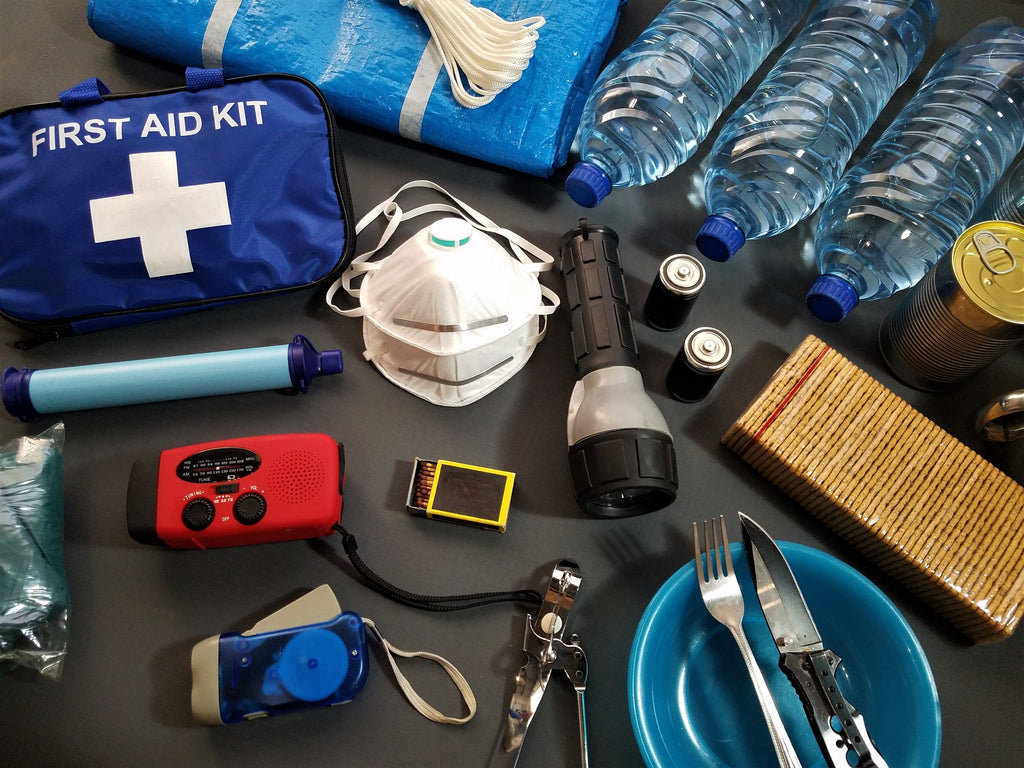 An emergency supply kit shows a first aid kit, flashlight, mask, utensils, and water bottle.