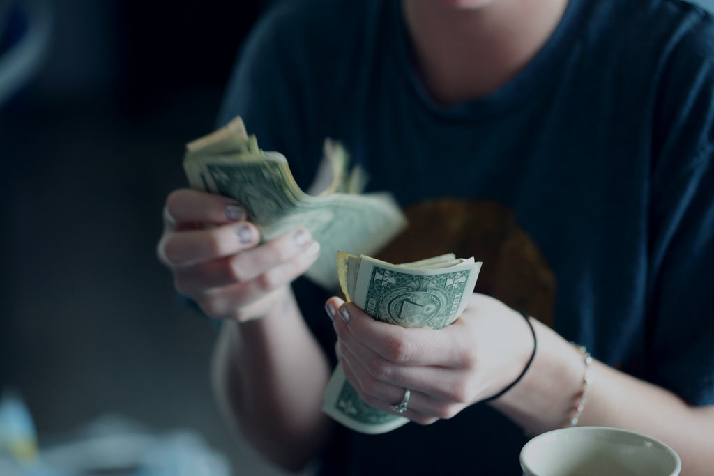 A person holds paper money in their hands and counts it.