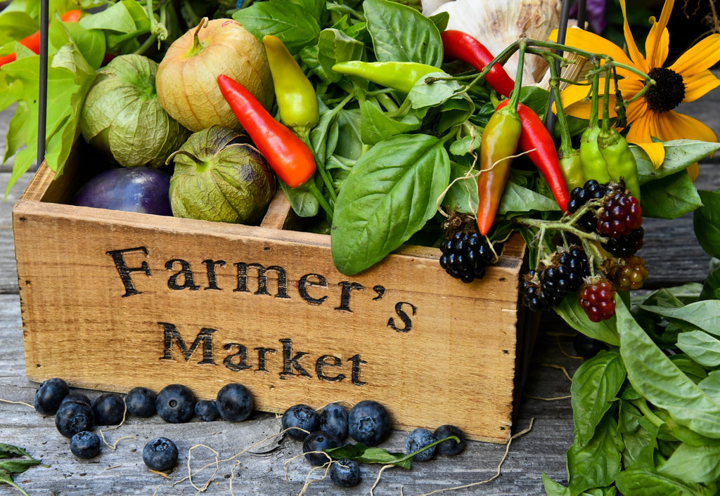 The image shows a wood basket that says Farmers Market filled with fruits and vegetables.