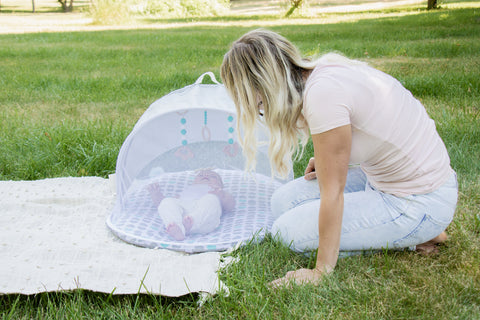 mom outside with little baby on a play mat