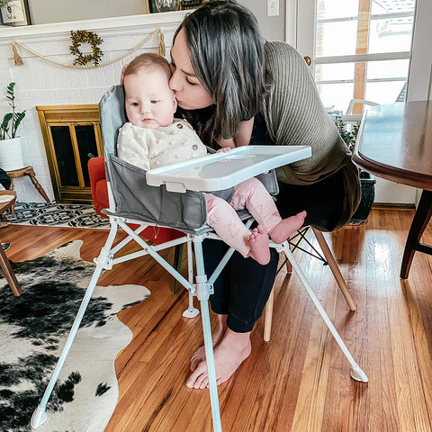 girl in a high chair with mom