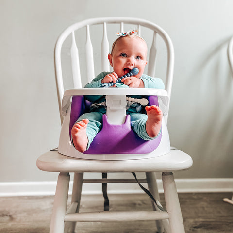 little girl sitting at the table in a booster seat