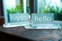 "Load image into Gallery viewer, Acrylic Card Holder shown with custom engraved acrylic cards that read ""happy"" and ""hello""."
