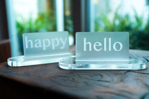 "Acrylic Card Holder shown with custom engraved acrylic cards that read ""happy"" and ""hello""."