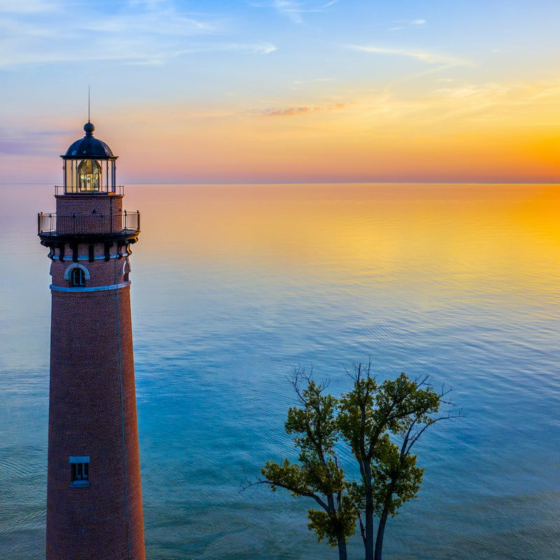 Close up view of Little Sable Point Lighthouse and ocean during sunset in Silver Lake State Park Michigan