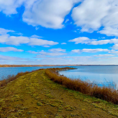 walking down the narrow grass strip surrounded by water at Alum Creek State Park