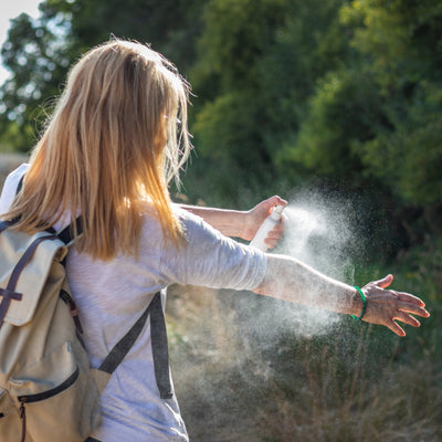 girl spraying insect spray on herself while camping