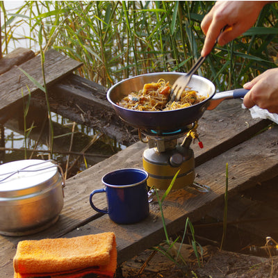 making noodles on a stove pan while camping
