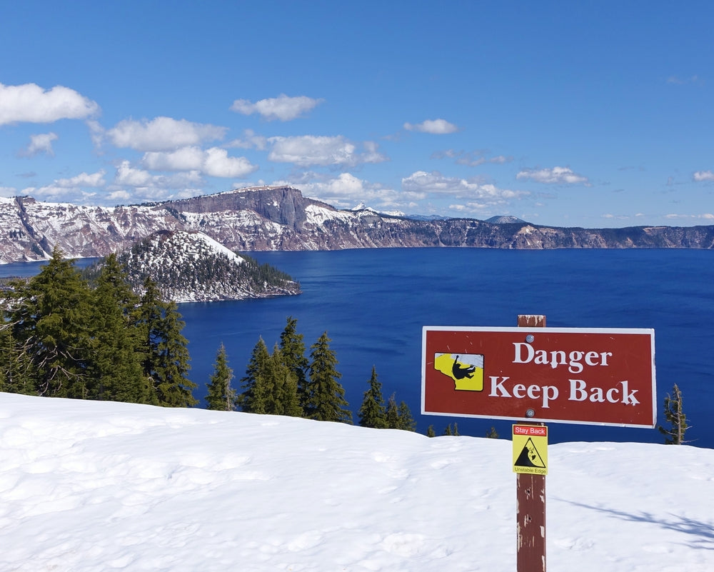 Danger Sign Along Snowy Slopes Looking Out Over Lake in Crater Lake National Park