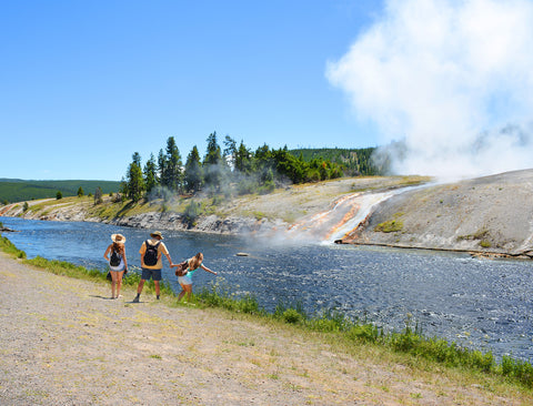 Family hiking next to Firehole River in Yellowstone National Park