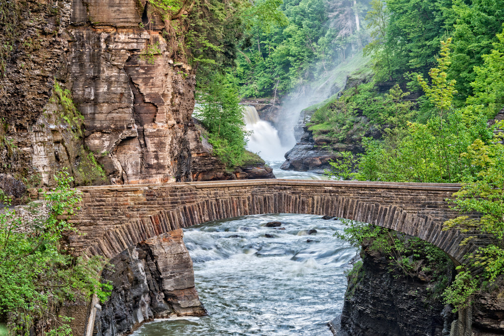 Grand canyon bridge going over river near lower falls waterfalls in Letchworth State Park NY