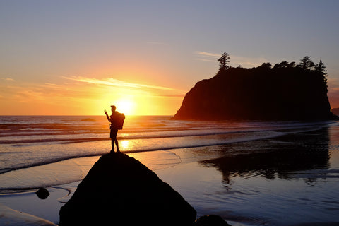 Hiker watching sunset over Ruby Beach in Olympic National Park