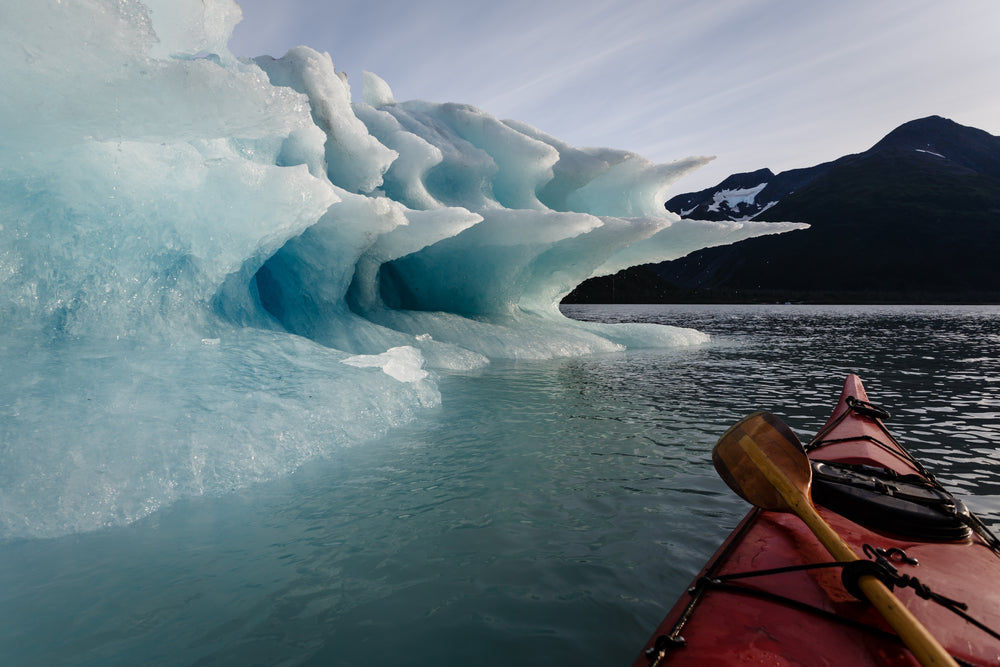 Kayak Floating Towards Melting Iceberg in Kenai Fjords National Park