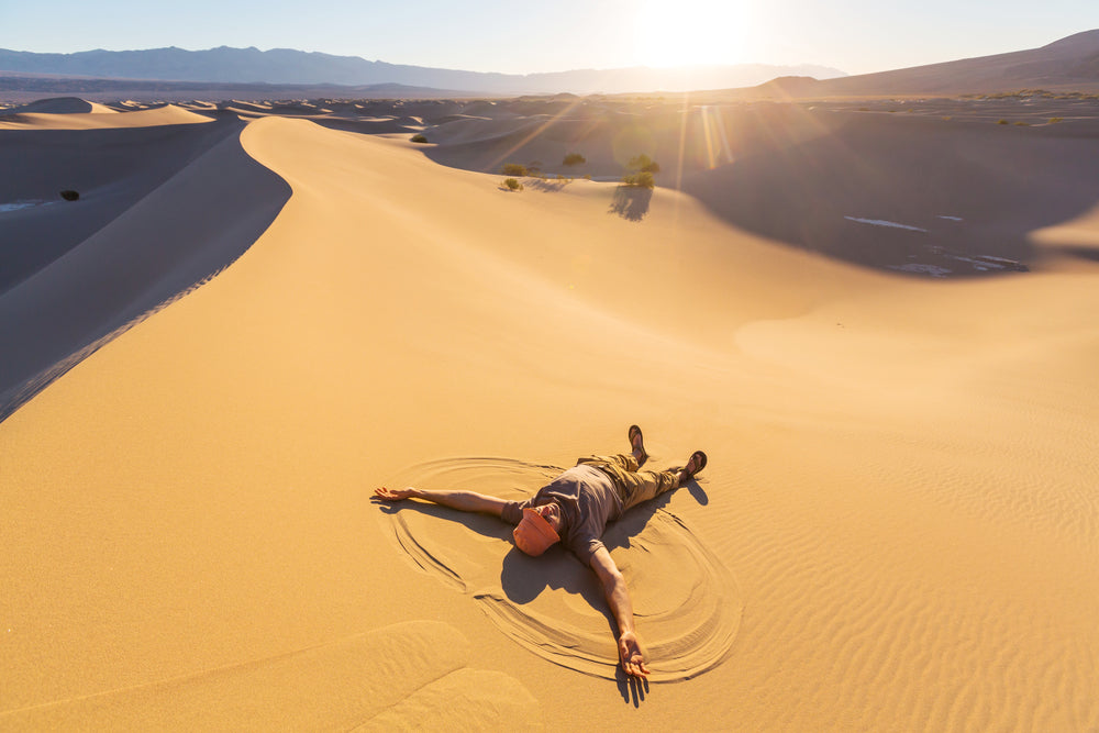 Man Making Sand Angel on Sand Dunes in Death Valley National Park California USA