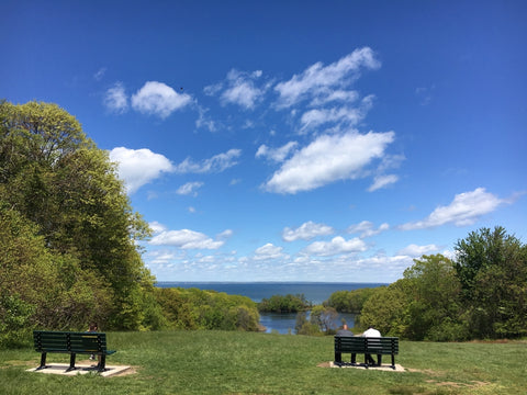 Park visitors sitting on benches overlooking Long Island Sound