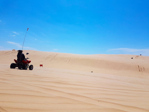 Person driving quad in off road recreation area around sand dunes in Silver Lake State Park Michigan