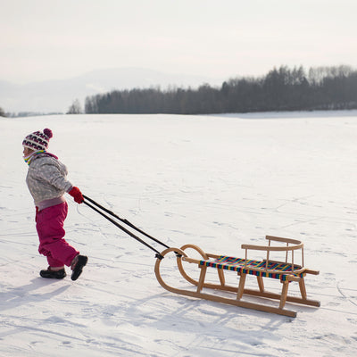 little girl walking sled on her way to go sledding at Chain o' Lakes State Park