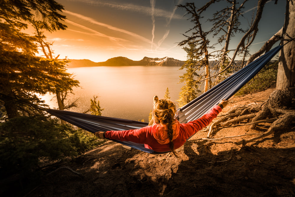 Woman Hiker Resting in Hammock Looking Out Over Crater Lake National Park in Oregon