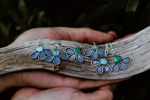 An image of a handful of echinacea medicine necklaces featuring Royston turquoise.
