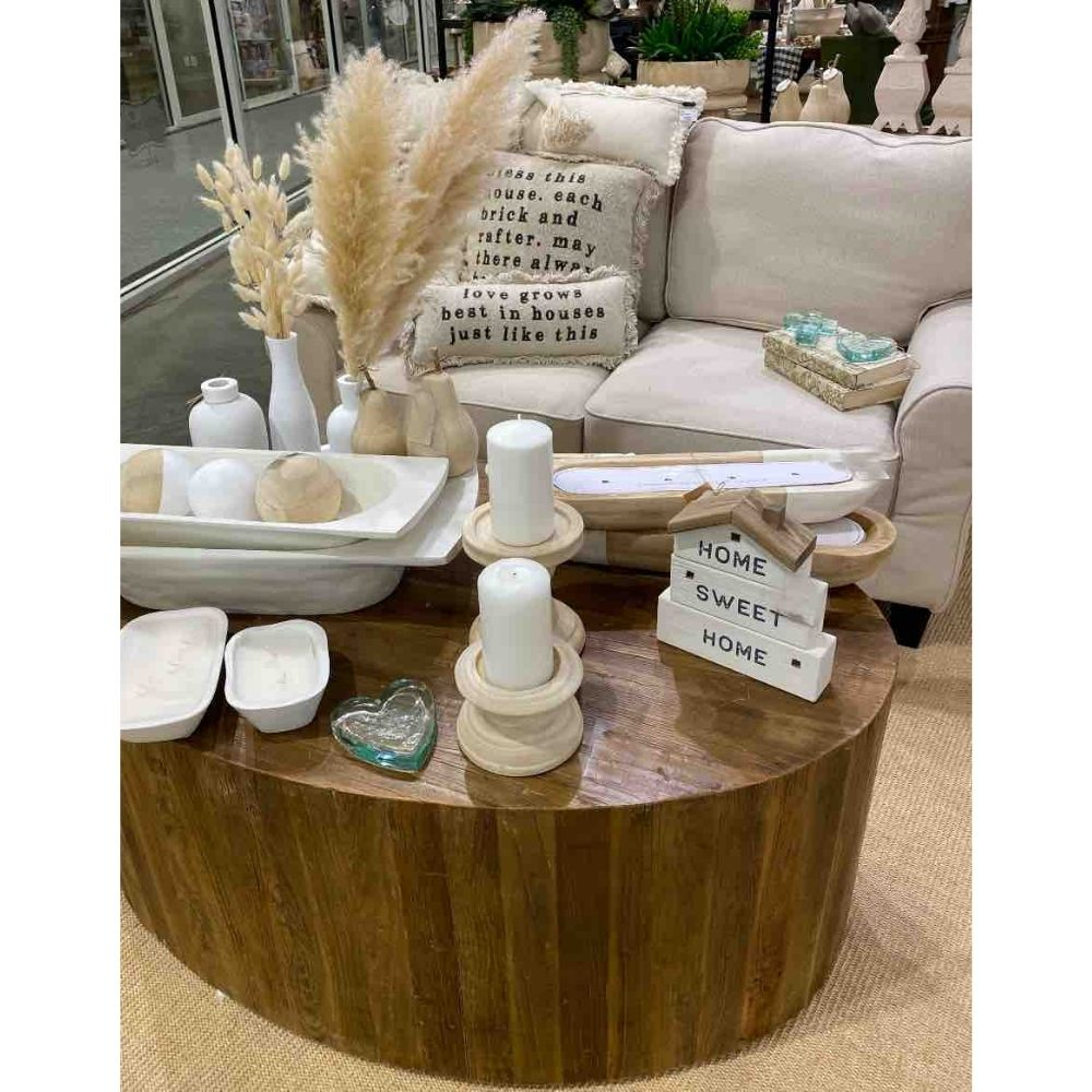 Home decor trends include natural and white accessories shown here on round wood coffee table next to white linen sofa