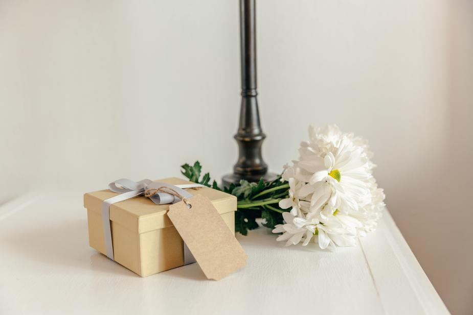 Gift on side table wrapped in natural paper with white flowers