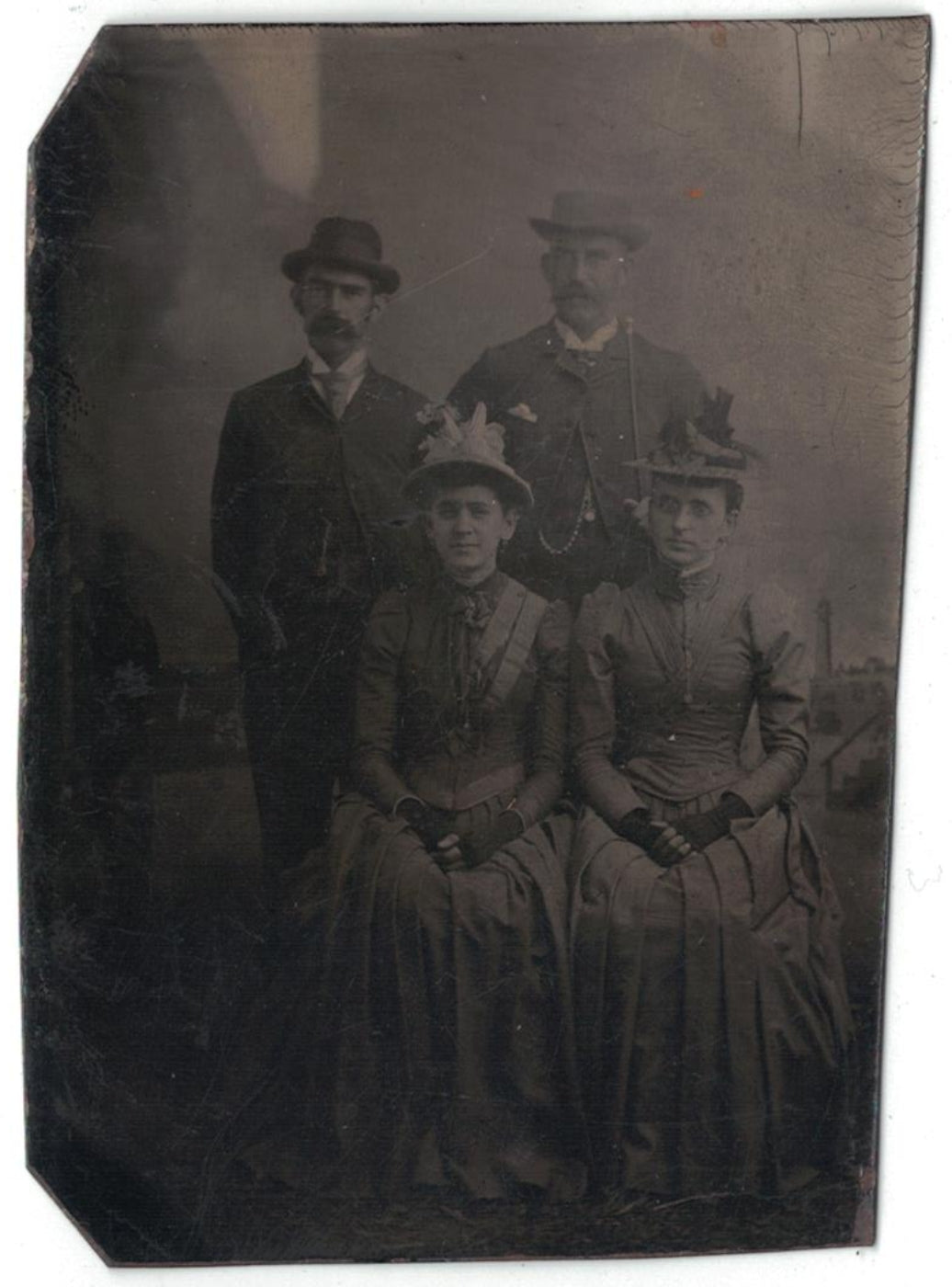 Antique tin type photograph two prominent looking couples.
