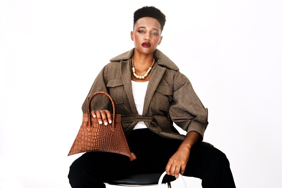 A photoshoot with MICRO BLANKET WHISKEY CROC is a micro brown bag, small bag with a croc look from MDLR