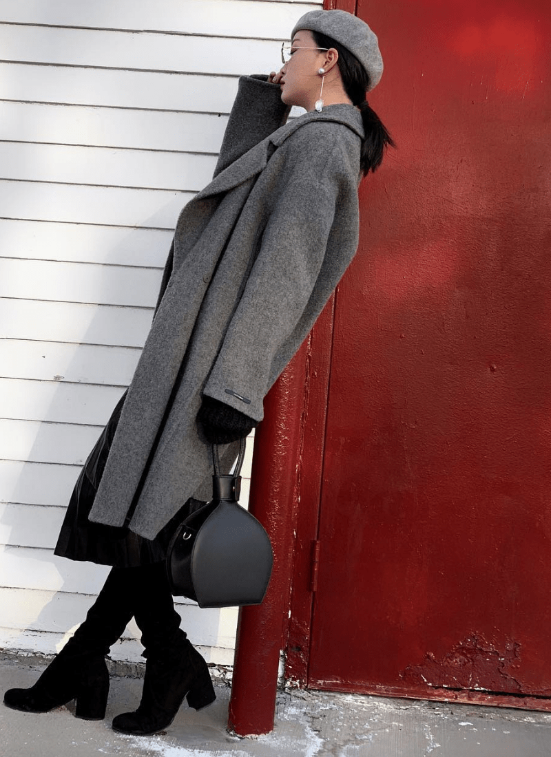 a woman in winter look holding ATENA BLACK PURSE-SLING BAG - MDLR